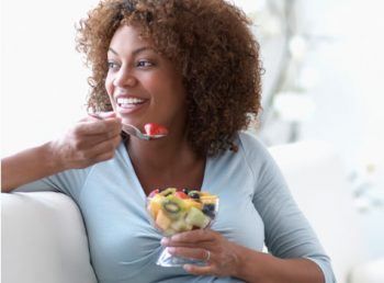 woman with healthy skin eating a bowl of fruit