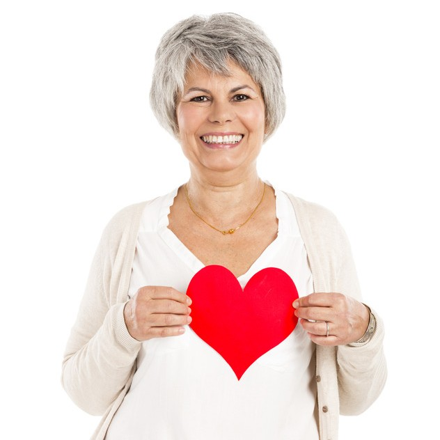 older woman holding a paper heart and smiling