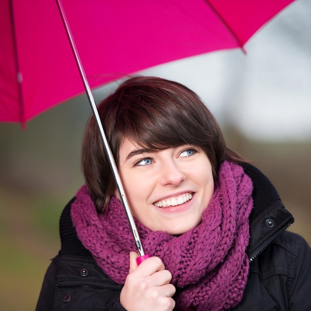 Happy woman under a pink umbrella and wrap