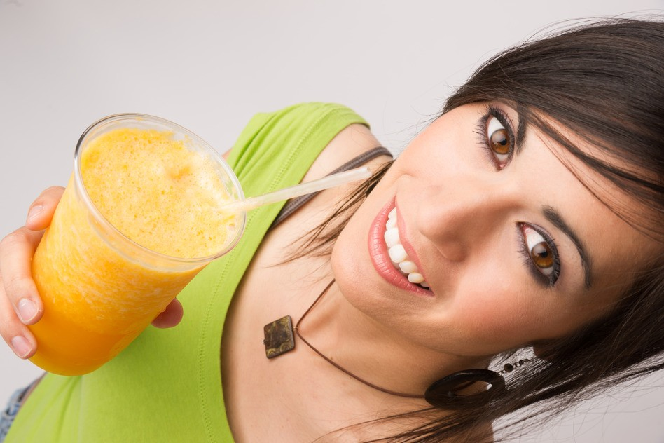 A beautiful woman enjoys a smoothie during a detox cleanse