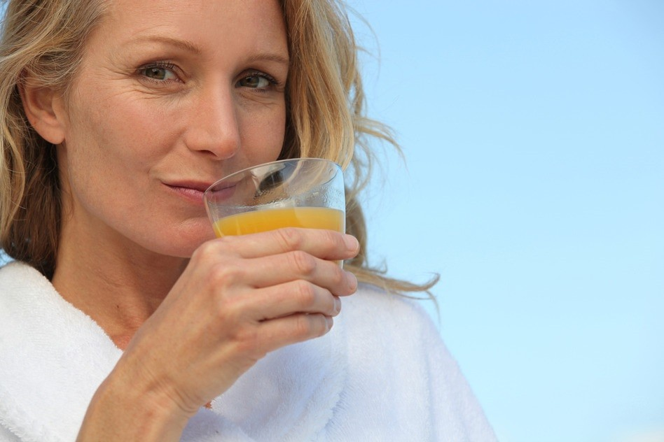 Woman drinking glass orange juice with collagen drink mix