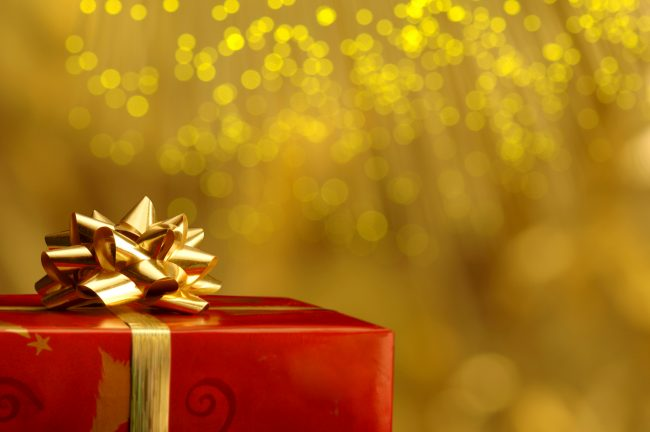 red gift with gold bow and ribbon with sparkling golden background